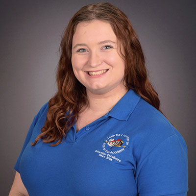 Samantha Bindler happy teacher wearing blue school shirt at a Preschool & Daycare/Childcare Center serving Miami, FL.