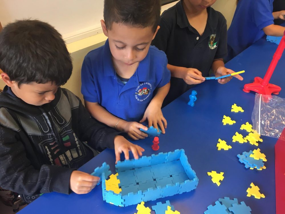 Group of young kids playing with puzzle building block at a Preschool & Daycare/Childcare Center serving Miami, FL.