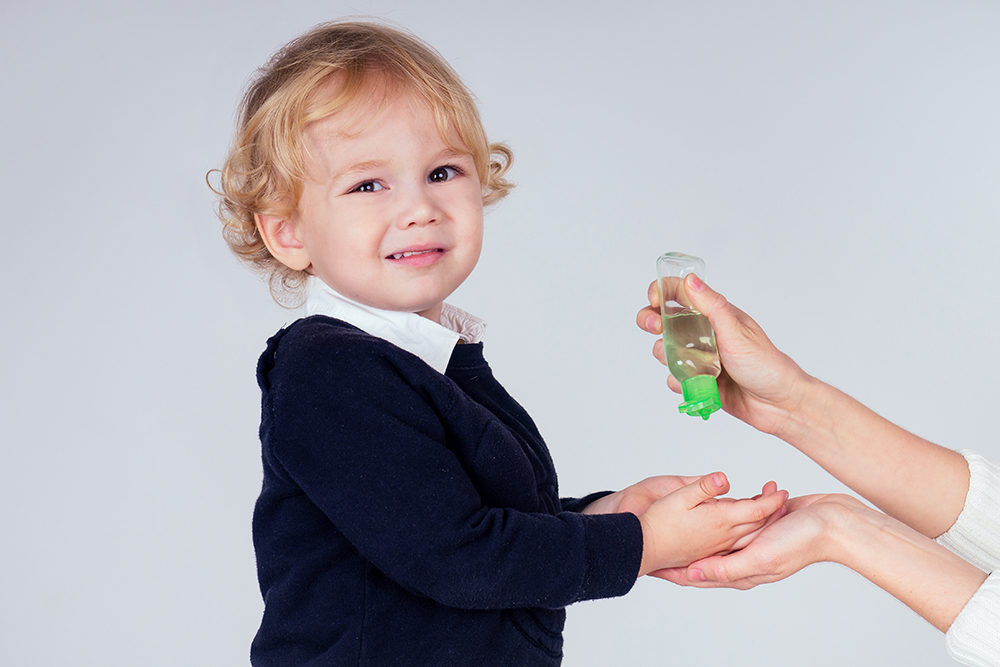 portrait of a cute little blond boy applying antibacterial antiseptic gel on hands anti bacteria viruses in studio on white background. baby epidemic protection,close-up mother's hand at a Preschool & Daycare/Childcare Center serving Miami, FL.