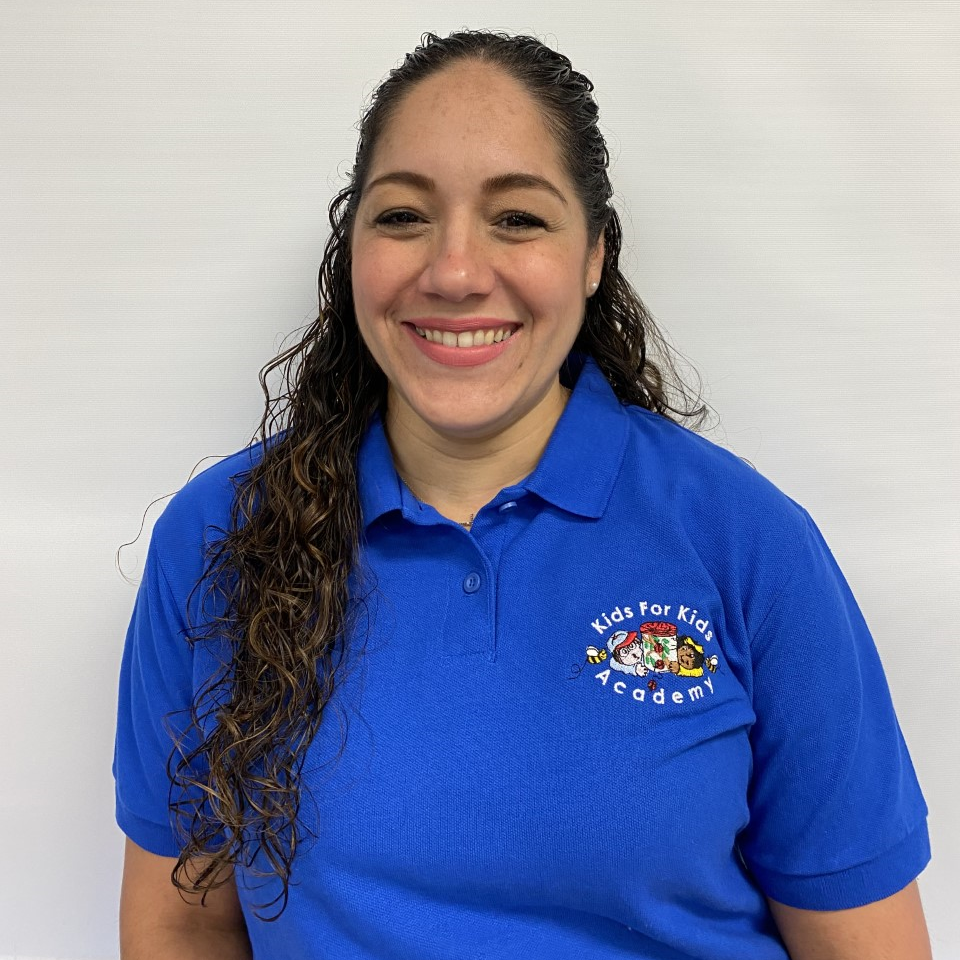 Giannina Maldonado happy teacher wearing blue school shirt at a Preschool & Daycare/Childcare Center serving Miami, FL.