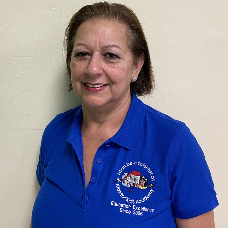 Miriam Salas happy teacher wearing blue school shirt at a Preschool & Daycare/Childcare Center serving Miami, FL.
