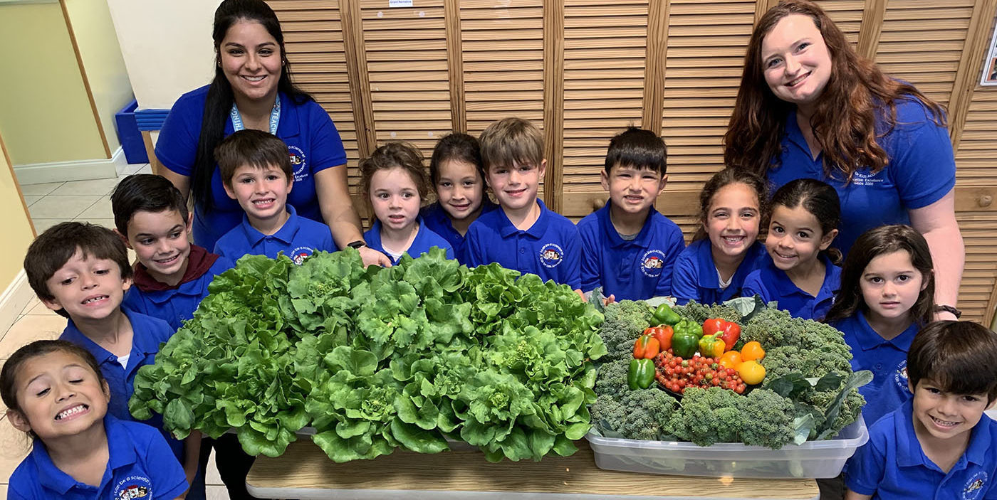 teachers and preschool kids holding vegetables at a Preschool & Daycare Serving Miami, TX